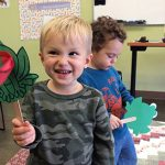 Two toddler boys with frog crafts at Little Paws Story Time
