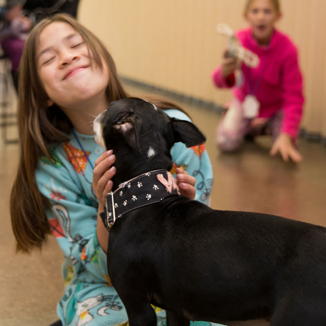 Girl in pajamas with dog kissing her